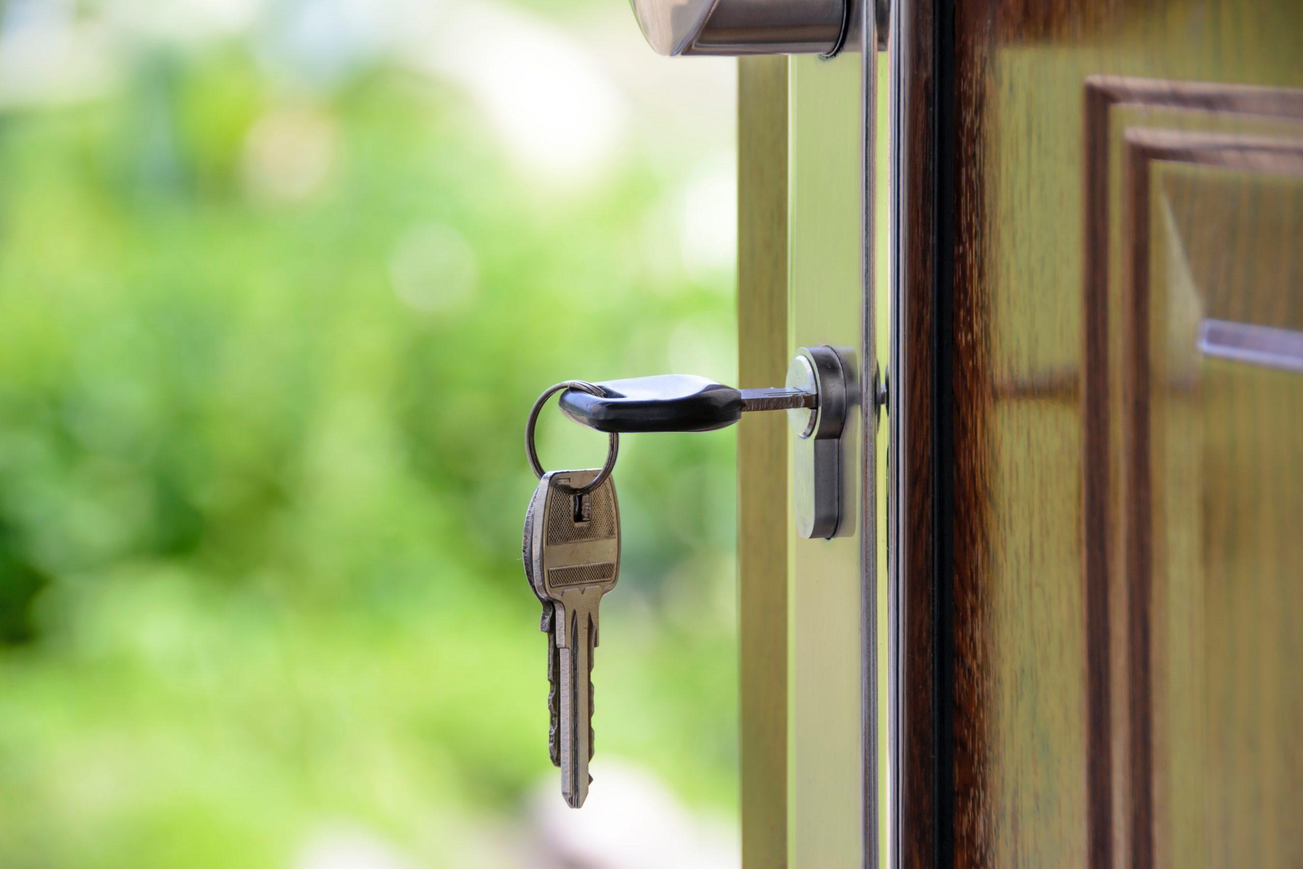 Open door with key hanging from lock