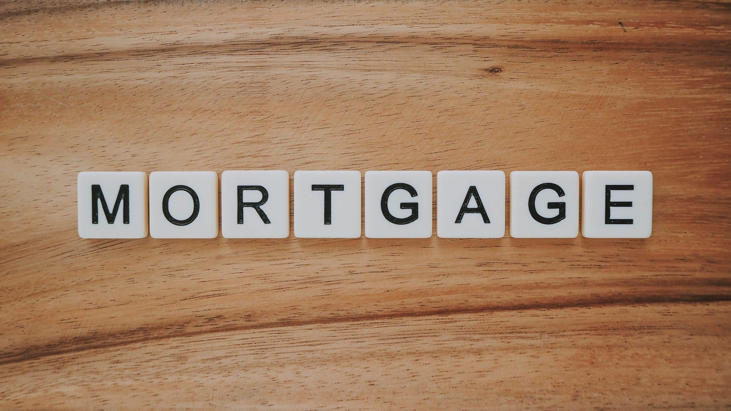The word mortgage spelt out in scrabble tile letters on a wooden background